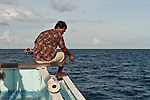 Captain Mu'in drives the mother boat. He also joins his crew in catching yellowfin tuna with hook and line from a fishing boat.