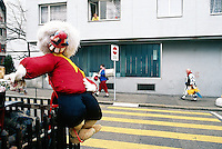 """Switzerland. Basel. Fasnacht Carnival. An old woman looks out of her apartment's window musicians from a """"Clique"""" walking on the road's pavement. A  """"Clique"""" is a group of persons playing music in the streets during the three days of the Fasnacht Carnival. A masked figure is tied on a wood fence.  © 1997 Didier Ruef"""