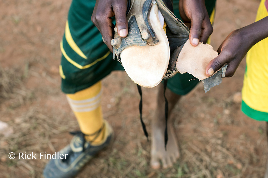 BURUNDI, Ruyigi: 10 June 2015 Ruyigi Re-education Centre Feature.<br /> See accompanying article for general information. <br /> Pictured: A boy shows his well-worn football boots that he has to play with. <br /> Rick Findler / Story Picture Agency