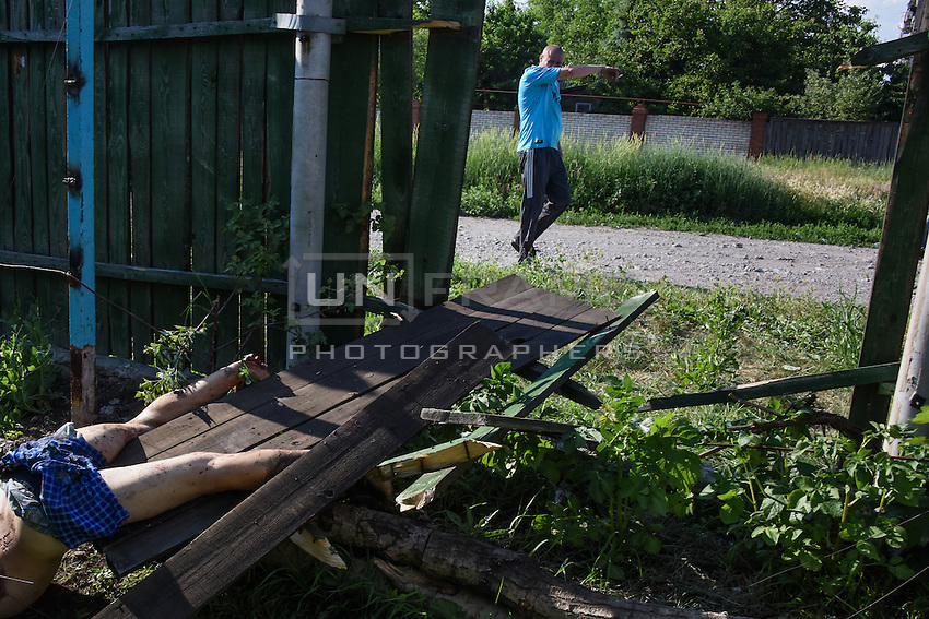 Man covers his face, when passing by the body of his friend killed by shelling in Donetsk, eastern Ukraine, Thursday, June 11, 2015.