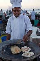 Forodhani Gardens, Stone Town, Zanzibar.  A Cook Prepares Zanzibari Pizza for Customers.