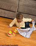 10 month old baby boy pulling cloth off hidden toy
