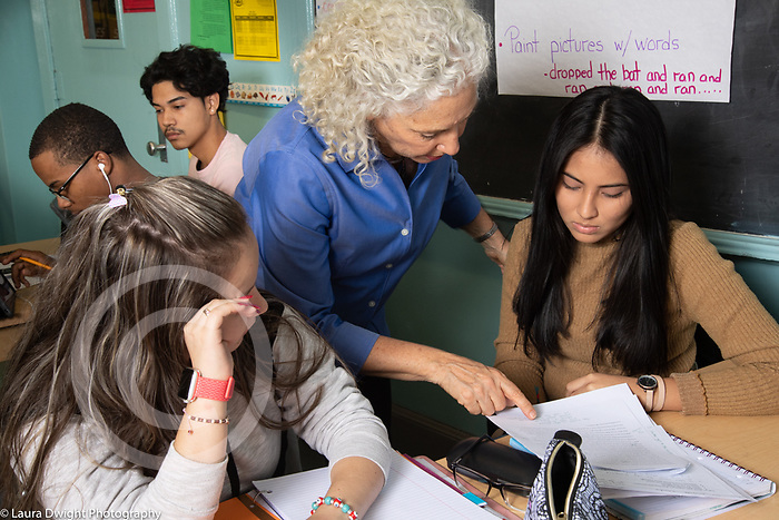 Education high school classroom scenes female teacher talking to female student about her work, classmate looking on