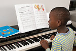 7 year old boy at home practicing piano