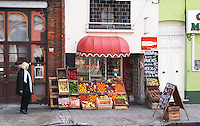 A grocery shop with fruits and vegetables on display on the pavement a woman walking on the street looking, oranges, apples, bell peppers, chalk boards advertising the products. Montevideo, Uruguay, South America