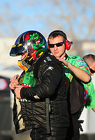 Feb. 17 2012; Chandler, AZ, USA; NHRA top fuel dragster driver Terry McMillen (left) gets help from crew member Austin Lambright as he gets suited up during qualifying for the Arizona Nationals at Firebird International Raceway. Mandatory Credit: Mark J. Rebilas-