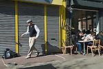 Hackney, Chatsworth Street, man doing street dance, people enjoung Sunday moring cup of coffee. London UK
