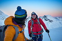 Two women ski touring stopped and laughing, Switzerland.
