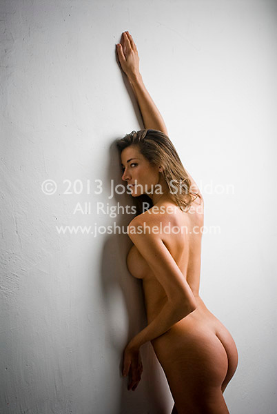 Nude woman stretching up wall