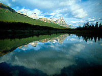 Art in Nature 9607-0214 - A body of a water, surrounded by evergeen trees, reflects the Northern Rocky Mountains background and sky in Banff National Park. Alberta, Canada.