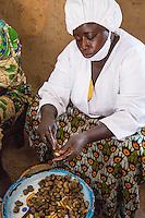 Woman Hulling Cashew Nuts at Cashew Nut Processing Center, Group Dimbal Djabott, Mendy Kunda, North Bank Region, The Gambia