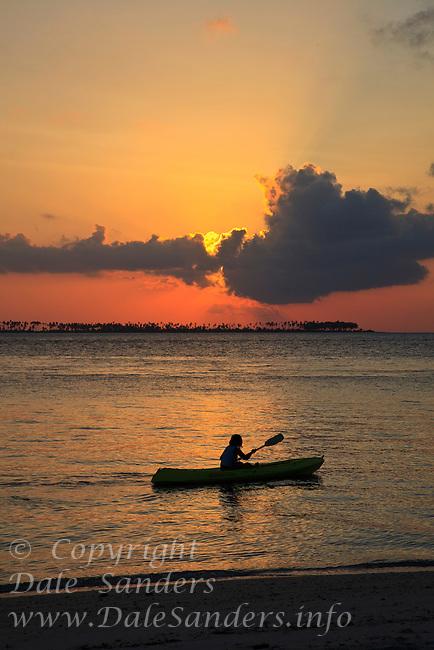 Sunset over kayaker at Wakatobi Dive Resort, Southeast Sulawesi, Indonesia.