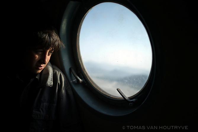 A boy looks out a Pakistani helicopter window at flood damaged while flying to the village of Bahrain in the Swat valley, Pakistan, on Aug. 27, 2010. The roads and bridges leading to Bahrain have been completely cut off by the floods.