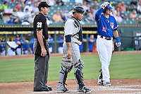 Humberto Quintero (35) express displeasure  over interference call by official Jeff Morrow as Round Rock Express third baseman Ryan Rua (12) arrives to bat during pacific coast league baseball game, Saturday August 16, 2014 in Round Rock, Tex. Tacoma Rainiers win game one of the best of four series 8-7. (Mo Khursheed/TFV Media via AP Images)