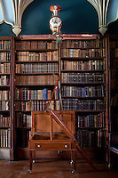 An ingenious ladder that folds out of a table to gain access to the upper shelves of the library bookcases