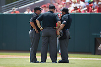 Home plate umpire Eric Loveless (right) confers with the rest of his crew during the game between the Northeastern Huskies and the North Carolina State Wolfpack at Doak Field at Dail Park on June 2, 2018 in Raleigh, North Carolina. The Wolfpack defeated the Huskies 9-2. (Brian Westerholt/Four Seam Images)
