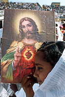 Eritrea. Asmara. September square. Meskel is the most important religious feast for the orthodox church in Eritrea. It takes place every year on september 27. A young girlwith a white cotton loincloth on her face  carries a picture of Jesus adult . She holds the holy image (God reprsentation) close to her cheek. The public is seated on the terrraces. © 2002 Didier Ruef