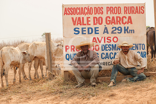 "Para State, Brazil. Two gauchos - cowboys - with their cattle in front of a sign which says ""Association of rural producers Vale do Garca, main farm office 29kms""."