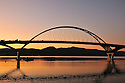 The graceful arch of the newly constructed Champlain Bridge in Addison, Vermont frames the Adirondacks at sunset.