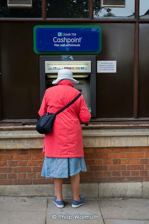 Elderly woman using a cash machine, Hamsptead, London.