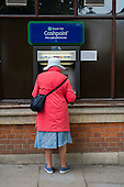 Elderly woman using a cash machine, Hamsptead, London.