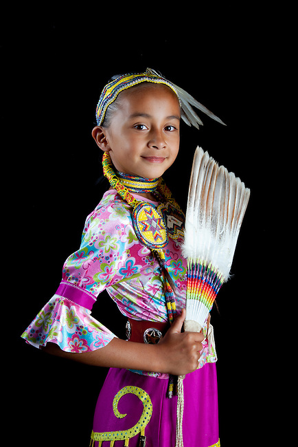 Traditional pow wow dancer 9 year old Jaydean (Lakota) dressed in colorful regalia and beaded hair band holds up a feather fan against a black background.