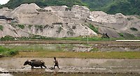 A farmer and water buffalo in front of  the Yun Chang Ping Mercury Mine in the mountains about 30 kilometers from Tongren city, Guizhou, China.
