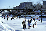 Ice skating on Rideau Canal World Heritage Site, Ottawa, Ontario, Canada with Parliament Buildings in backgroiund