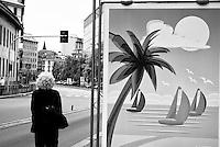 Milano, estate. Un pannello pubblicitario con il disegno stilizzato di una spiaggia con una palma, il mare con tre barche a vela e il sole, lungo una strada deserta con una donna bionda di spalle dai capelli ricci --- Milan, summer. A billboard with the stylized drawing of a beach with a palm, the sea with three sailing boats and the sun, alongside an empty road with a blond woman  with curly hair