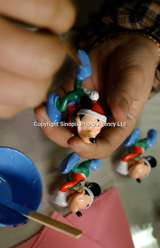 Workers at Taifu (Fuzhou) Co. Ltd, hand-paint disney toys in Fuzhou City, China. The Taiwanese-owned factory makes jewellery and hand-painted toys and figures for overseas companies..02-MAR-04