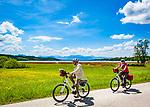 Deutschland, Bayern, Oberbayern, Rosenheimer Land, (Chiemgau), bei Rosenheim: Radfahrer auf dem Rundweg (ca. 20 Km) um den Simssee, im Hintergrund die Chiemgauer Alpen | Germany, Upper Bavaria, Rosenheimer Land, (Chiemgau), near Rosenheim: cycling around lake Simssee (20 Km), at background Chiemgau Alps