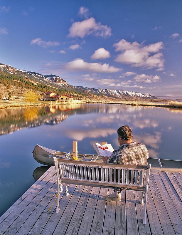 Reader on bench at pond at Summer Lake Inn, Oregon