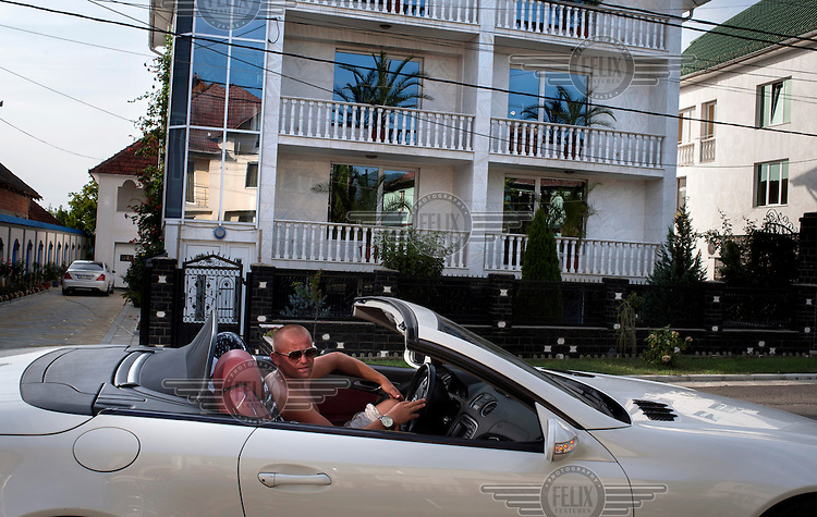 Petre Dorle drives around his native village in his white Ferrari. Petre has become a very successful businessman in France where he hires workers from Romania to come and work in the construction industry. ..