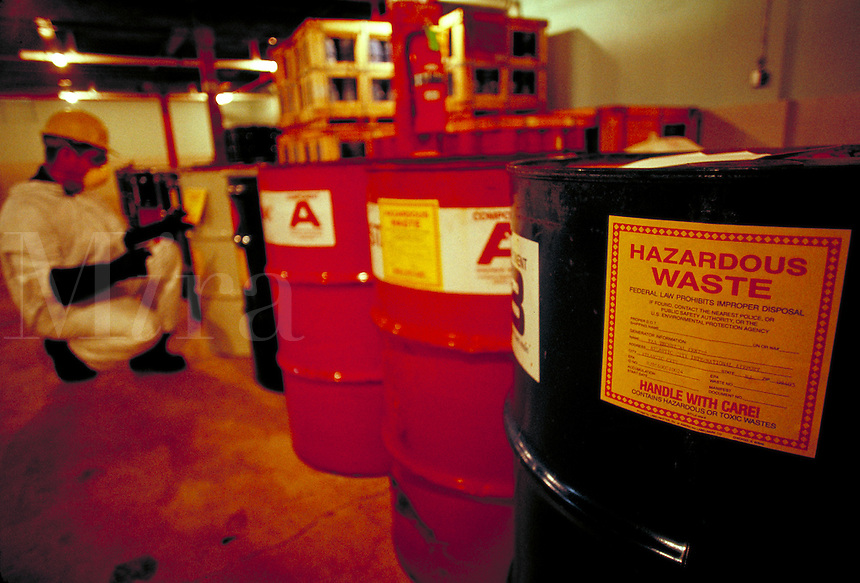 Close up of 55 gallon barrel of hazardous waste with person in protective clothing kneeling in backround. RB0486025. environment. protection. pollution. FAA Research facility at Atlantic City airport.