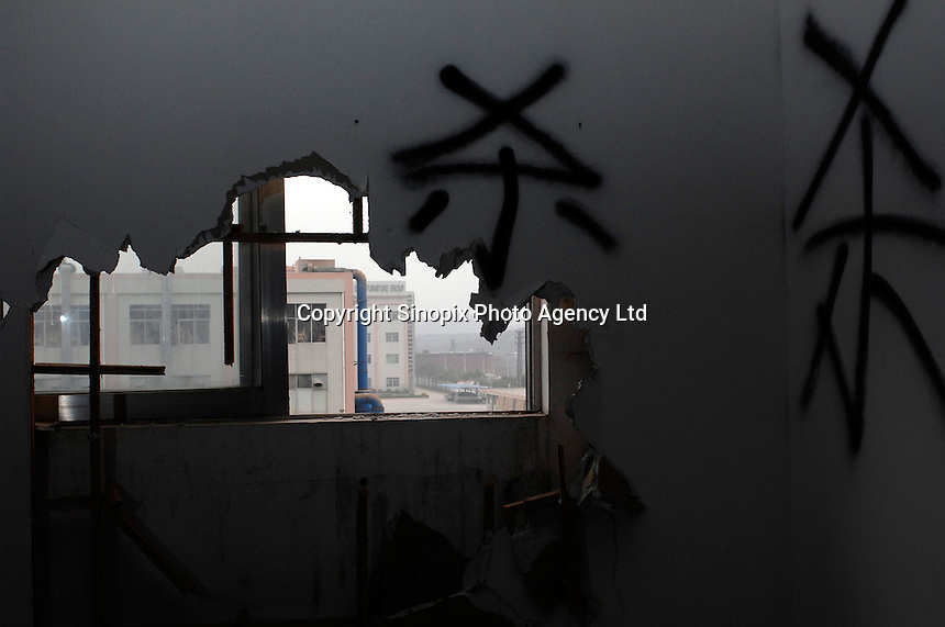 "A deserted factory in Houjie Town, Dongguan, China. The graffitti on the walls reads ""kill"". Many of the factories closed leaving workers unpaid. The workers dstroyed some factories. As the economy changes and Chinese labour gets more expensive, factories are closing leaving ghost towns behind them..20 Dec 2007"