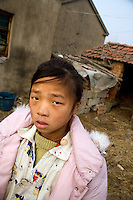 Sun Lu Lu, 11, was orphaned in 1999, and was left to live with her grandmother Li Ru Chun (right, about 70 years old) in Wang Dong Village, Jiangsu Province, China.  The girl's father died from disease in 1998.  The girl's mother had been purchased for a dowry from a family in the western provinces of China and was forced to remarry in 1999, abandoning the girl.  The girl rarely speaks to her grandmother, who is in poor health and cannot provide financial, material, or emotional support for the girl.  ..At the time of these pictures, China's Amity Foundation charity, was investigating the family's situation in preparation to raise money to financially support these children and other orphans in similar situations.  With Amity's support, each orphan, aged 6-12, would receive approximately 1,400 RMB annually (about 200 USD) to pay for the cost of living. Amity works to keep children out of the institutional orphanages in China, preferring to provide monetary assistance that can help maintain a family environment for the orphans it helps.