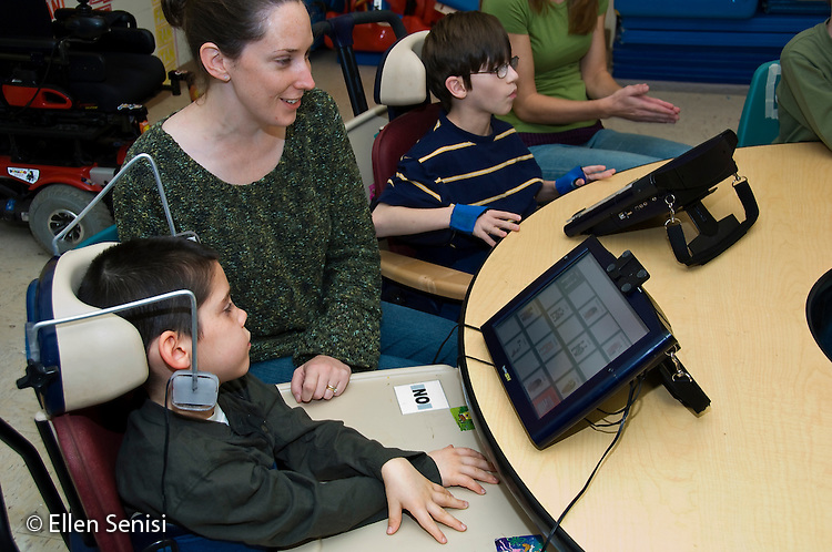 MR / Albany, NY.Langan School at Center for Disability Services .Ungraded private school which serves individuals with multiple disabilities.Speech language pathologist works with student during speech and language lesson. She is helping him use his augmentative and alternative communication device. Boy: 8, cerebral palsy, spastic quadriplegic, nonverbal with expressive and receptive language delays.MR: Hac2, Dub1.© Ellen B. Senisi