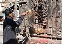 Kathmandu, Nepal.  Nepali Man Performing Prayer Ritual at a Shrine in the Swayambhunath Temple Complex.