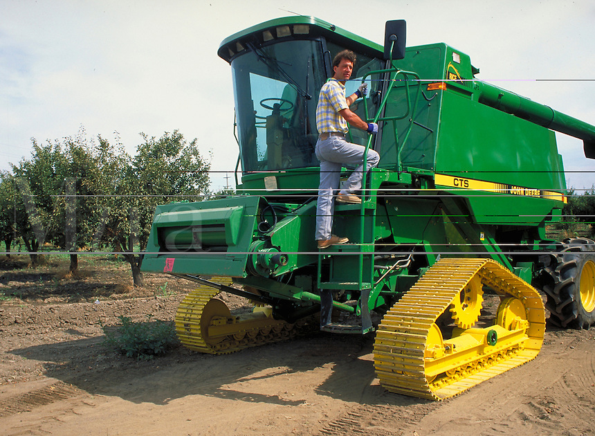 young farmer climbing on to green harvester equipment. farmer. California.
