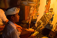 Denpasar, Bali, Indonesia.  Young Boy Reciting Story being Acted out by Shadow Puppets he Controls.  Pura Jagatnatha Temple, Wayang Kulit Performance.