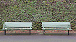 Two wooden benches in front of stone wall.