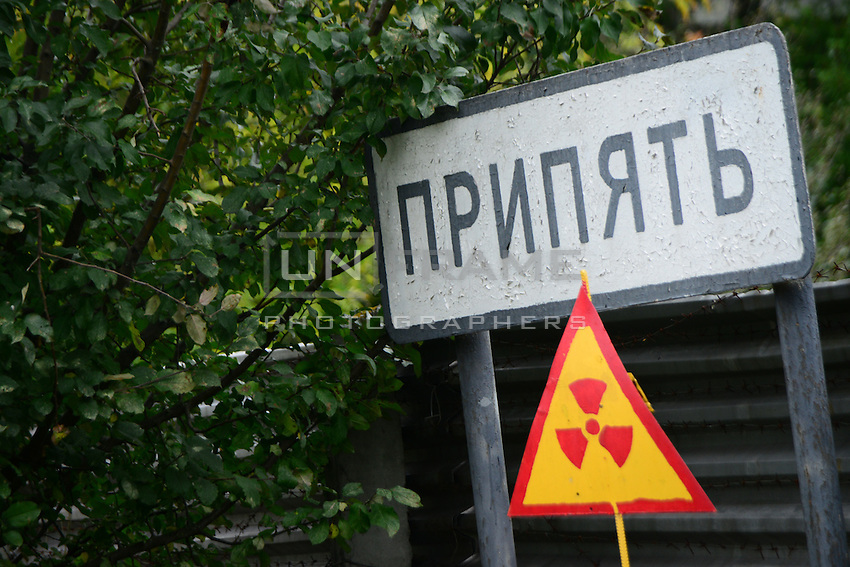 Warning sign alongside with sign with name of city Pryptat at the entrance to it's abandoned territory