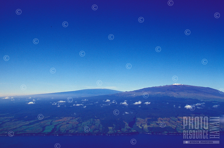 Aerial view of snow capped Mauna Kea with observatories, and Mauna Loa in background.