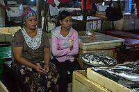 Bali, Indonesia.  Mother and Daughter Waiting for a Customer, Jimbaran Fish Market.