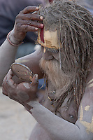 Pashupatinath, Nepal.  Sadhu (Holy Man) at Nepal's Holiest Hindu Temple.  He checks himself in a mirror as he begins to paint his face.