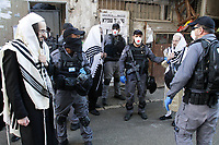 Haredis o temerosos de dios cubiertos con el manto de rezo o talit, son detenidos por la policia antidisturbios en el barrio ultra ortodoxo Mea Shearim mientras rezaban a tempranas horas de la maniana en una sinagoga, violando la prohibicion impuesta por el Ministerio de Salud de rezar en sinagogas durante el confinamiento decretado como parte de la lucha contra el COVID 19. Las autoridades israelies declararon la ciudad  ultrareligiosa Bnei Brak y los barrios ultra ortodoxos de Jerusalén bajo sitio en un esfuerzo por controlar el contagio de la pandemia.<br /> Foto Quique Kierszenbaum