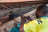 Nungwi, Zanzibar, Tanzania.  Dhow Construction.  With a hand-powered drill a carpenter makes holes to receive nails or pegs to anchor the outer planks to the inner supporting ribs of the hull.