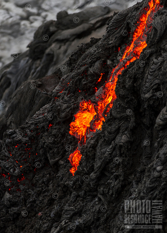 Lava flows down a lava tube into the sea from a dangerous cliff, so close the heat was extremely intense, near Hawai'i Volcanoes National Park and the Kalapana border, Big Island.