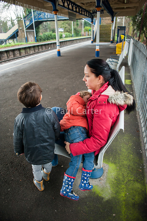 A mother breastfeeding her three and a half year old boy at a train station.<br /> <br /> Surrey, England, UK<br /> 03/01/2015<br /> <br /> © Paul Carter / wdiip.co.uk