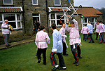 "BRITISH COUNTRY CUSTOMS, ""GOATHLAND PLOUGH STOTS"" YORKSHIRE. TEENAGE BOYS IN COSTUMES DANCING WITH SWORDS- FORMED STAR IN GARDEN."